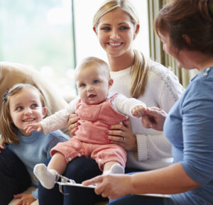 Woman holding an infant with young girl sitting next to her - Parent Child Interaction Therapy (PCIT)