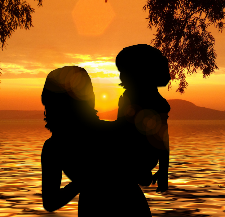 Mother holding child on beach in sunset