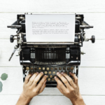 hands typing at manual typewriter with paper in it