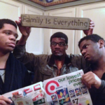 "three young men with Target ad and ""family is everything"" sign"