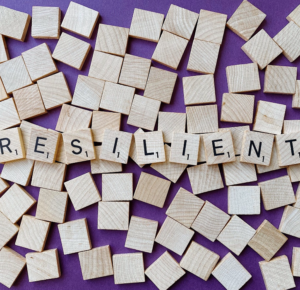 scrabble tiles spelling resilient on a purple background