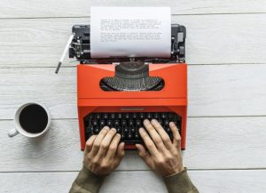 hands typing on orange old-fashioned typewriter